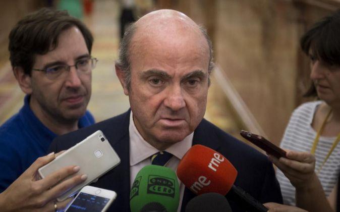 El ministro de Economía, Luis de Guindos, realiza declaraciones a los periodistas en los pasillos del Congreso el pasado martes.