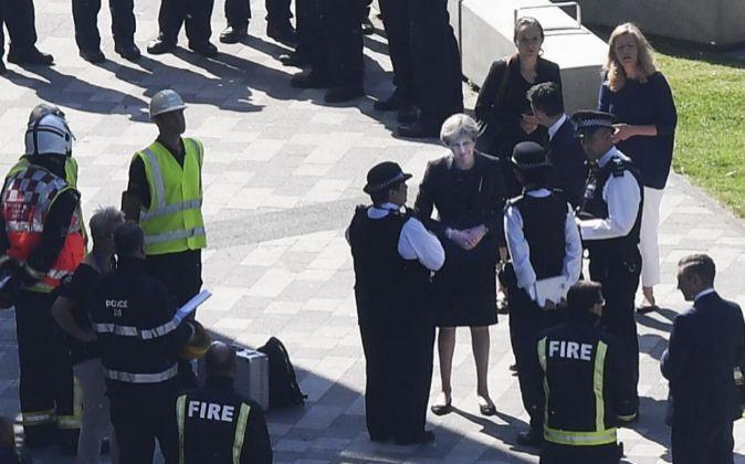 La primera ministra británica, Theresa May (c), conversa con agentes...