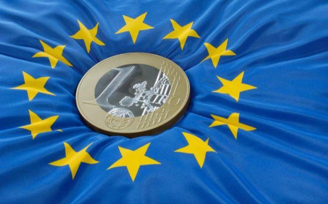 Moneda de euro sobre la bandera de la Unión Europea.