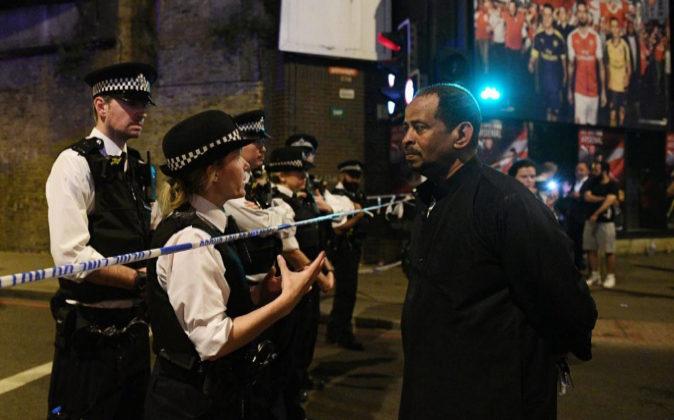 Agentes de policía informan a un transeúnte tras cordón policial...