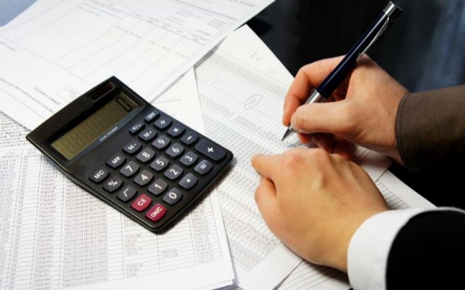 Mano de un hombre con una calculadora, haciendo la Declaración de la...