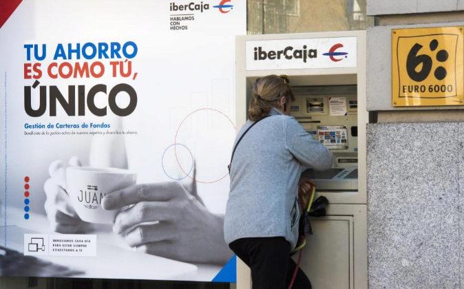 Una mujer saca dinero en una sucursal de Ibercaja.