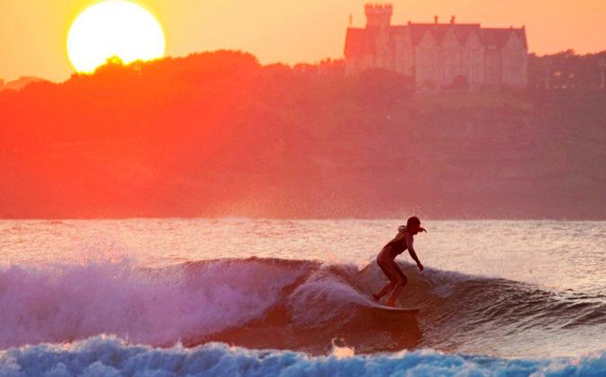 Imagen de un surfista con el Palacio de la Magdalena (Santander) como...