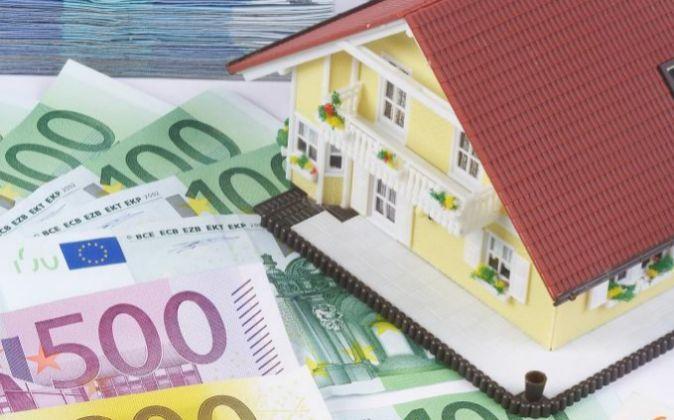 Maqueta de una vivienda sobre billetes de euro.