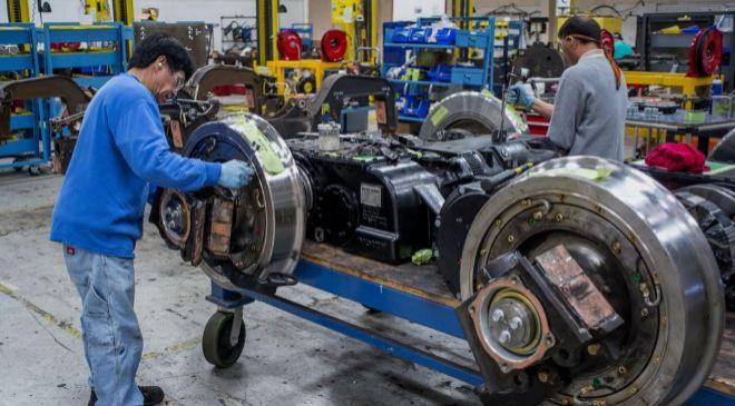 Empleados reparando ruedas de un tren Amtrak en la fábrica de Siemens...