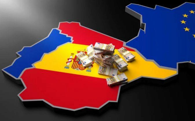 Fajos de billetes sobre un mapa de España.