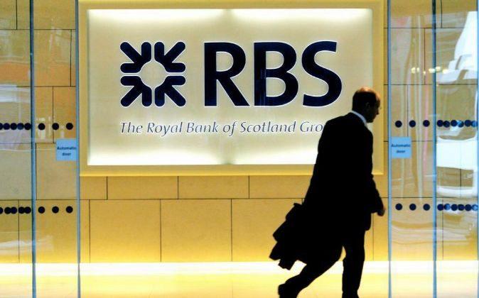 Un hombre camina frente a una sucursal del Royal Bank of Scotland.