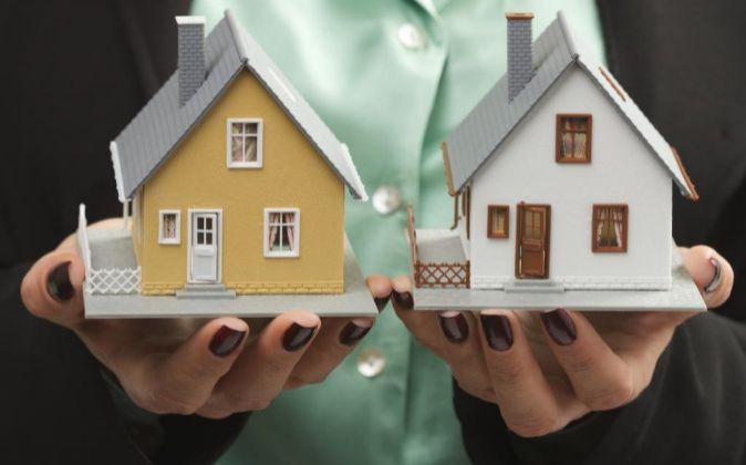 Una mujer sostiene dos maquetas de viviendas en sus manos.