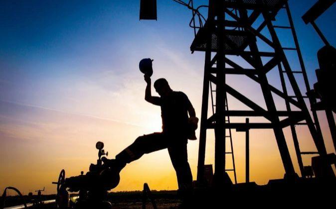 Un trabajador de una refinería junto a un pozo petrolífero.