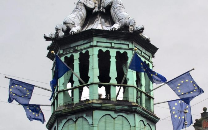 En la imagen, banderas de la Unión Europea ondean en un edificio...