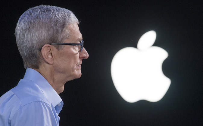 Tim Cook, CEO de Apple, junto al logo de la empresa.