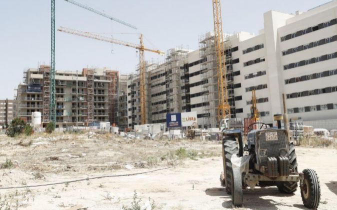 Viviendas en construcción rodeadas de grúas.