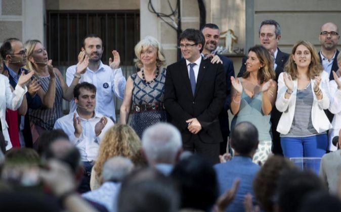 El presidente de la Generalitat, Carles Puigdemont (c), junto a la...