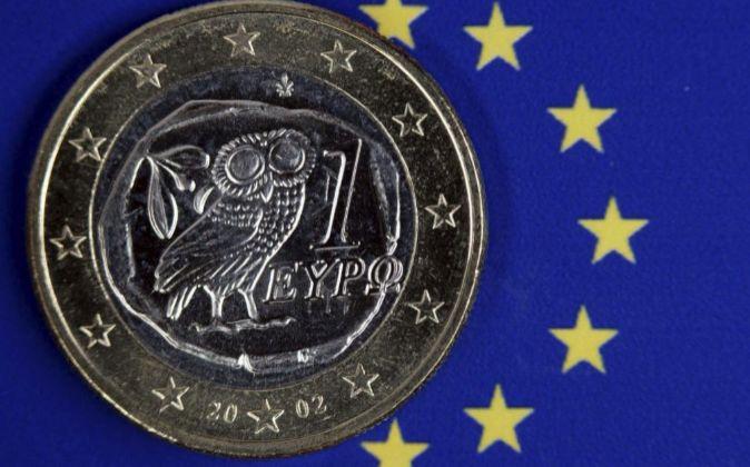 Moneda de 1 euro griega sobre una bandera de la Unión Europea.