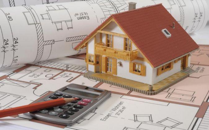 Maqueta de vivienda con planos y calculadora.