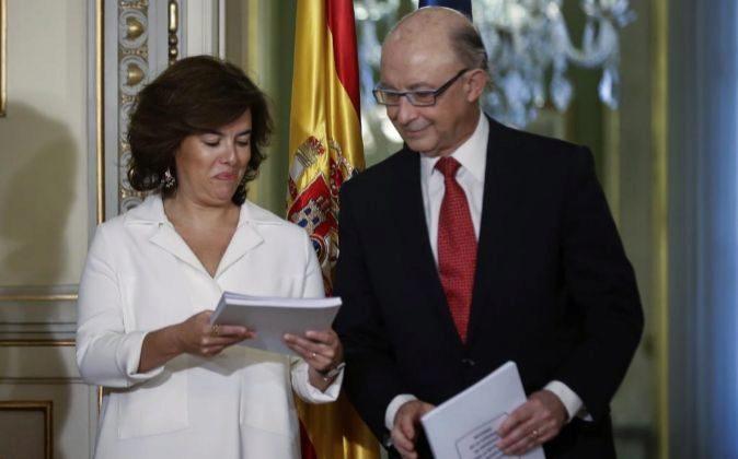 La vicepresidenta del Gobierno, Soraya Sáenz de Santamaría, y el...