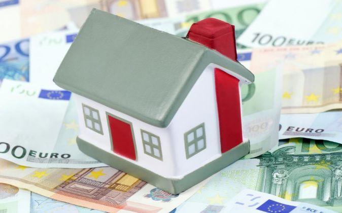 Maqueta de una casa encima de billetes de euro.
