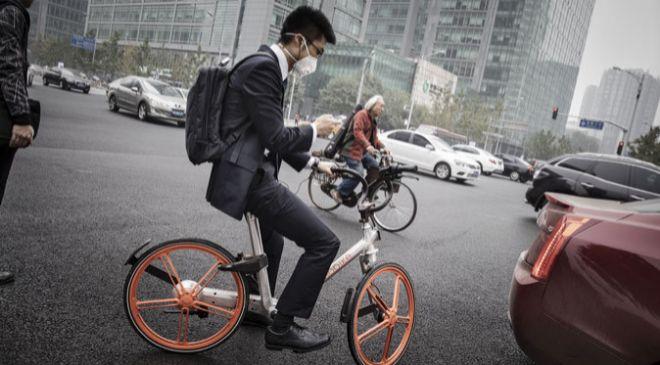 Un hombre monta una bicicleta de Mobike en Pekín, China.
