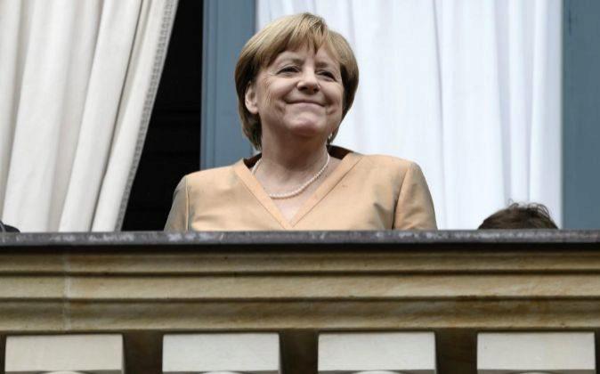 La canciller alemana, Angela Merkel, saluda al público a su llegada...