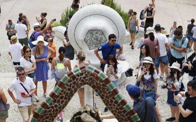 Numerosos turistas en la zona monumental del Park Güell de Barcelona.