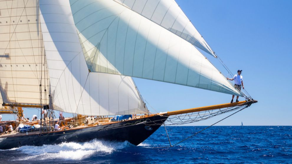 Un tripulante observa el campo de regatas sobre el bauprés de un...