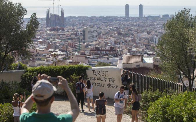 Un grupo de turistas pasea por los alrededores del Parque Guell de...