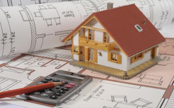 Maqueta de casa con unos planos y una calculadora.