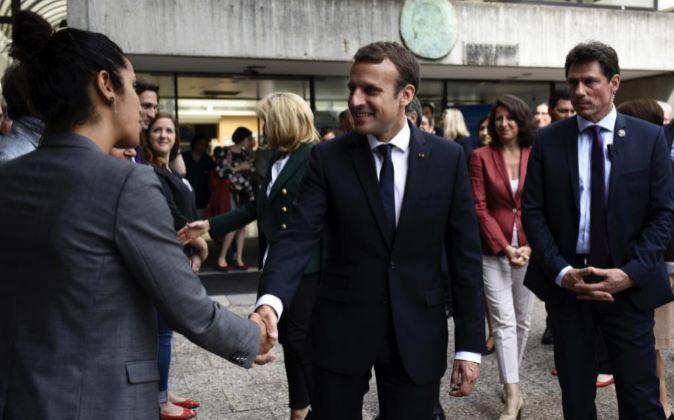El presidente francés, Emmanuel Macron (c), saluda a unos ciudadanos...