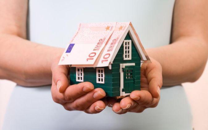 Manos que sujetan una casa con billetes en el tejado.