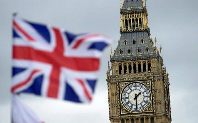 Una bandera británica ondea junto al Big Ben de Londres, Reino Unido,...