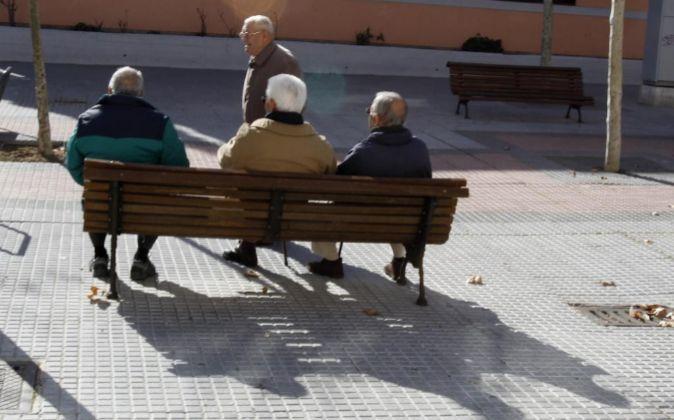 Aancioanos jubilados en un banco de una calle de Madrid.