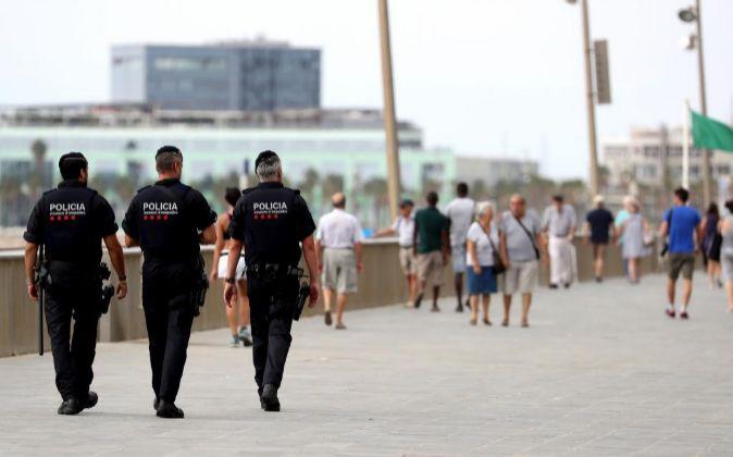 Agentes de los Mossos D'Esquadra patrullan por el paseo marítimo...