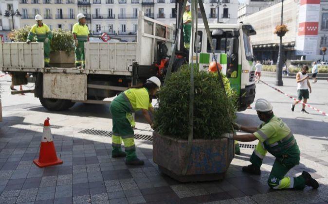 Operarios instalan jardineras en Madrid.
