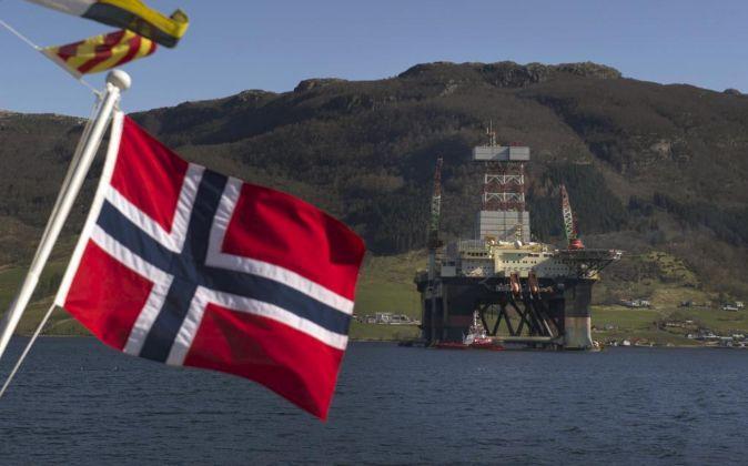 Bandera de Noruega frente a una plataforma petrolífera en Olensvag.