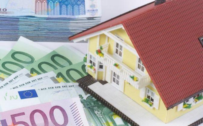 Maqueta de una vivienda con billetes de euro.