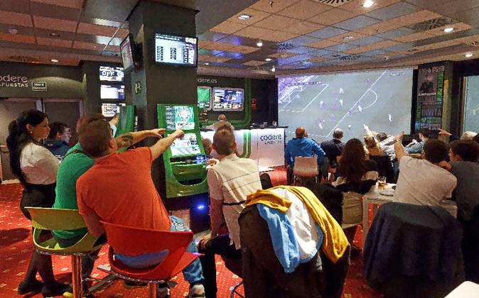Sala de apuestas deportivas durante la retransmisión de un partido de...