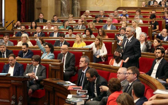 El pleno del Parlament vota ayer en medio de las protestas de algunos...