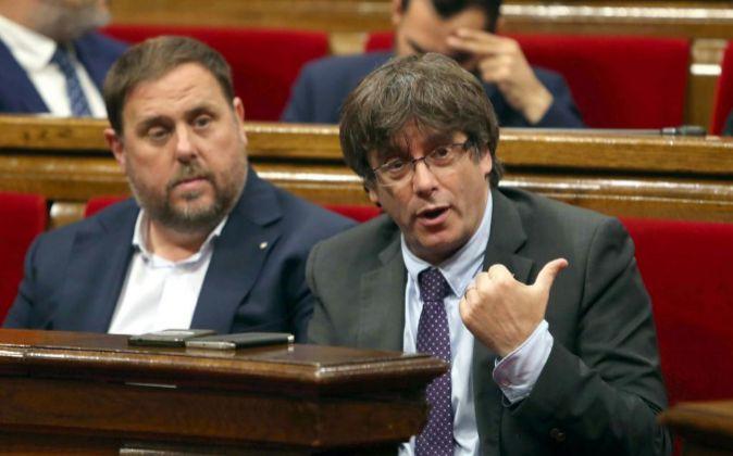 El presidente de la Generalitat, Carles Puigdemont (d) junto al...