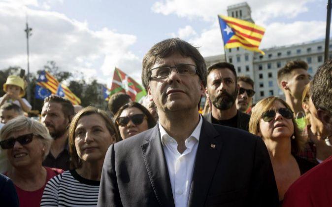 El presidente de la Generalitat de Cataluña, Carles Puigdemont (c), y...