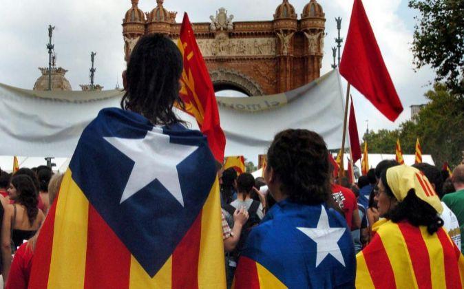 Varias personas portan la bandera independentista de Cataluña durante...