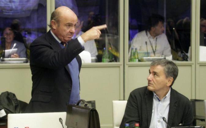 El ministro de Economía español, Luis de Guindos (i), habla con el...