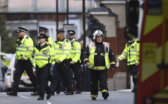 Bomberos y policías caminan junto a la estación de metro Parsons...