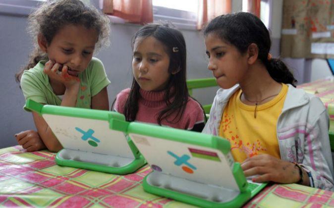 Niñas escolares uruguayas utilizan las computadoras del Plan Ceibal,...