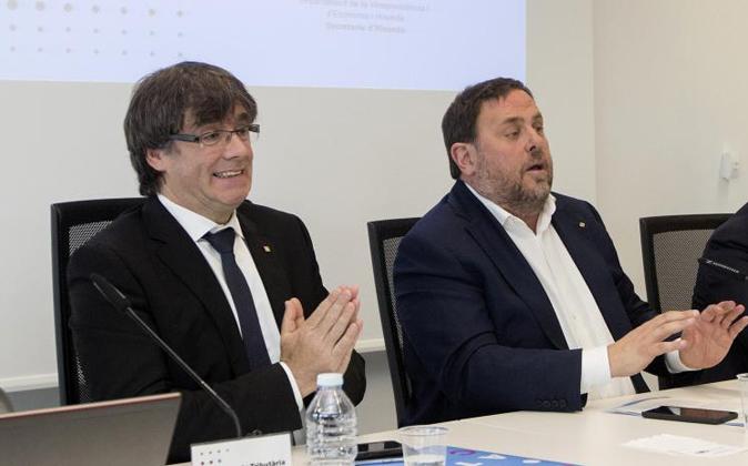 El presidente de la Generalitat, Carles Puigdemont (i), y el...