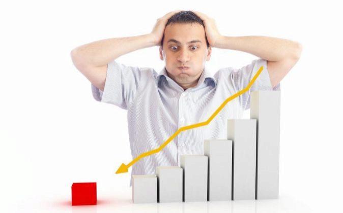 Un inversor preocupado mira la dirección descendente de una flecha.