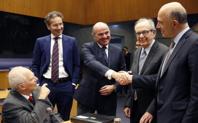 El ministro español de Economía, Luis de Guindos (c), estrecha la...