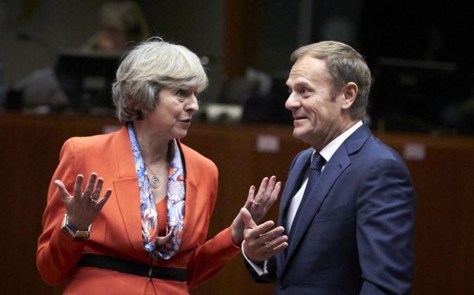 La primera ministra británica, Theresa May, conversa con el...