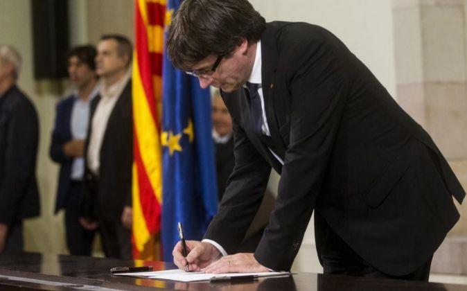 El presidente de la Generalitat, Carles Puigdemont, firma el documento...