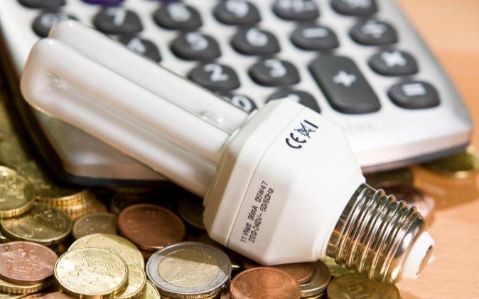 Bombilla sobre monedas de euros y una calculadora.