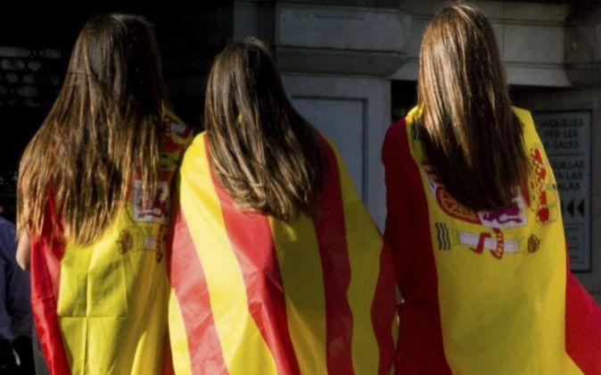 Tres jóvenes con banderas españolas y catalanas.